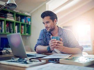 Hombre que ha aprendido cómo ganar más dinero trabajando desde casa con su ordenador