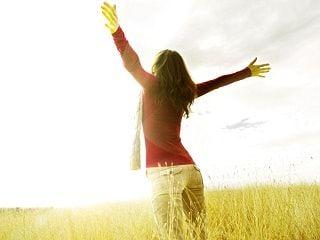 mujer que ha alcanzado el exito personal abre los brazos en un atardecer llena de felicidad