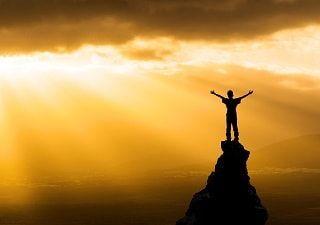 Persona exitosa en la cima de una montaña como representación de haber alcanzado el triunfo