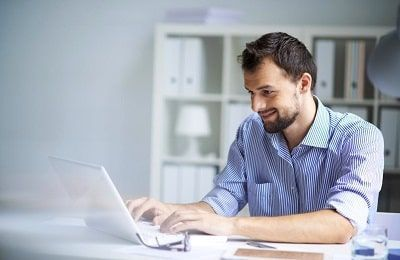 Hombre trabajando en su ordenador consiguiendo el exito profesional