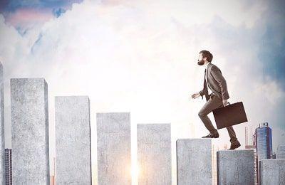 HOmbre en traje subiendo los peldaños del éxito como metáfora de las frases y la educación recibidas para alcanzarlo