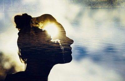 Silueta de cabeza de una mujer con el sol saliendo detrás simbolizando una reflexión profunda