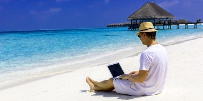hombre trabajando en la playa con un ordenador generando ingresos en vacaciones