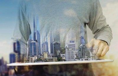 hombre sujetando una ciudad virtual de bienes raíces como simil del dinero que se puede ganar con el Real Estate