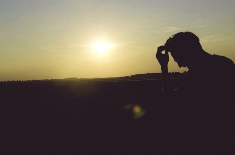 HOmbre con atardecer de fondo pensando en el objetivo de la vida para tener una vida con sentido