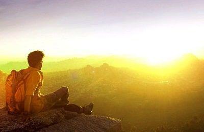 Montañista sentado viendo una preciosa puesta de sol mientras decide el proposito de su vida