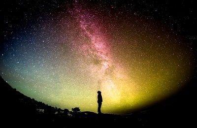 Persona mirando la galaxia preguntandose qué es el propósito de vida
