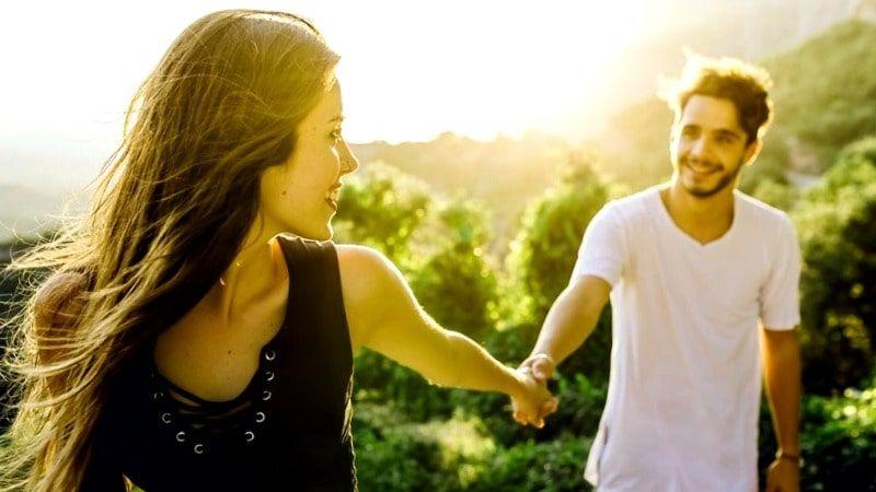 pareja de jóvenes en un bosque cogidos de la mano viviendo la vida al máximo y con propósito