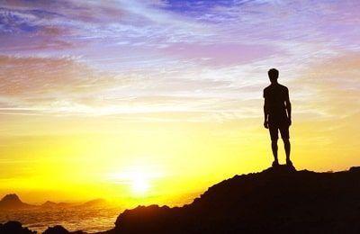 Hombre en lo alto de una montaña viendo el atardecer como simil del proposito en la vida