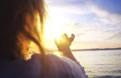 mujer mirando una puesta de sol con resolución para lograr lo que desea a pesar del miedo