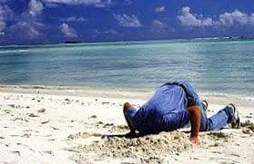 hombre enterrando la cabeza en la arena debido al miedo al fracaso que siente