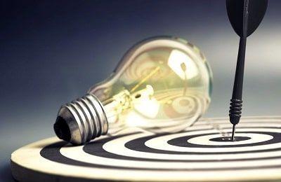 Bombilla iluminada encima de una diana como comparación a tener claros los objetivos personales