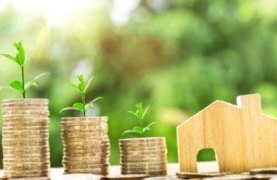 Maqueta de casa y montañas de monedas con plantas arriba para simbolizar las fuentes de ingresos crecientes y recurrentes