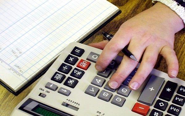 Calculadora mano y boligrafo de persona tomando el control de su situacion financiera