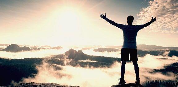 Mujer que ha realizado un proceso de superación personal alzando los brazos en señal de victoria